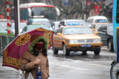 A Nanjing woman protects herself from the rain, the cold, and the airborne particles. Photo by Let Ideas Compete.