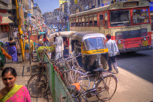 The traffic on the streets of Pune is busy with rickshaws, bicycles, buses and pedestrians. Flickr photo by wili_hybrid.