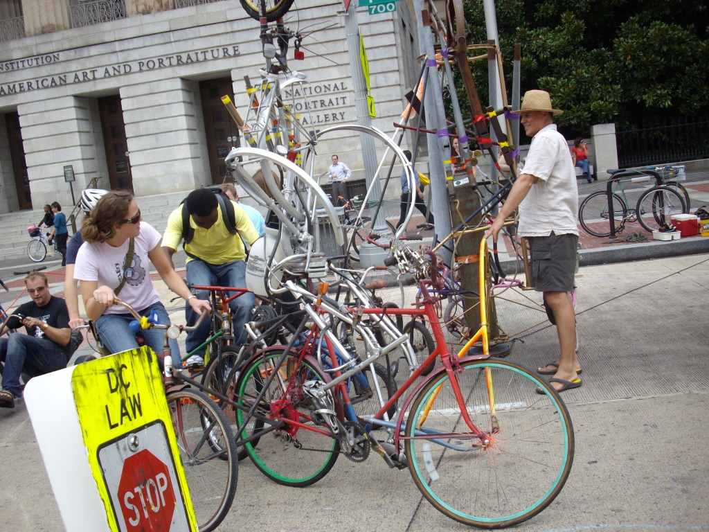 """Sculptor Howard Connelly (right) demonstrates his """"bicycle carousel."""" Photo by Patricio Chile."""