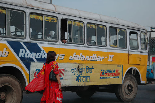 A woman prepares to board a bus outside of Delhi. Photo by Shawn Allen on Flickr.