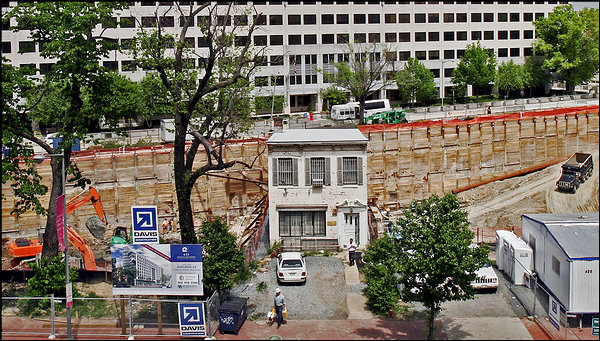 Austin L. Spriggs declined repeatedly to sell his aging rowhouse on Massachusetts Ave. in norwest Washington, DC to a condo developer. He ultimately held on to his property after it clung to the edge of a massive construction crater four stories deep. A condominium now wraps around the building on three sides and tower above it. Photo courtesy of the Washington Post.