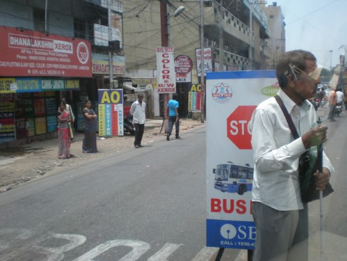 Inaccessible streets and transport systems in cities in developing countries can keep disabled people trapped in poverty. Above, a blind man tries to cross a street in Hyderabad, India. Photo via Robin King.