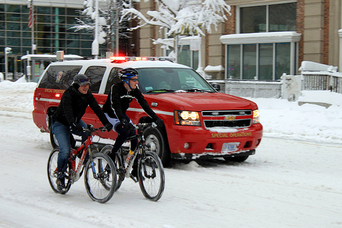 During a heavy blizzard, cars are nowhere to be seen; but cyclists and emergency vehicles stay the course. Photo by The Q.