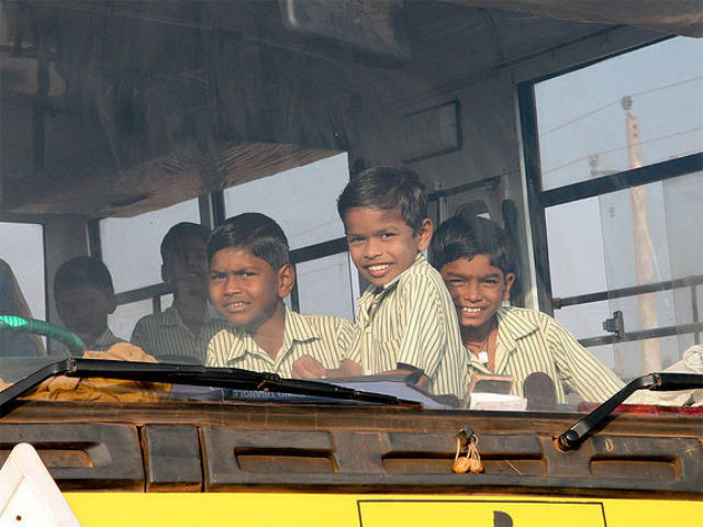 Children peer out a bus window in India. By marcusjroberts.