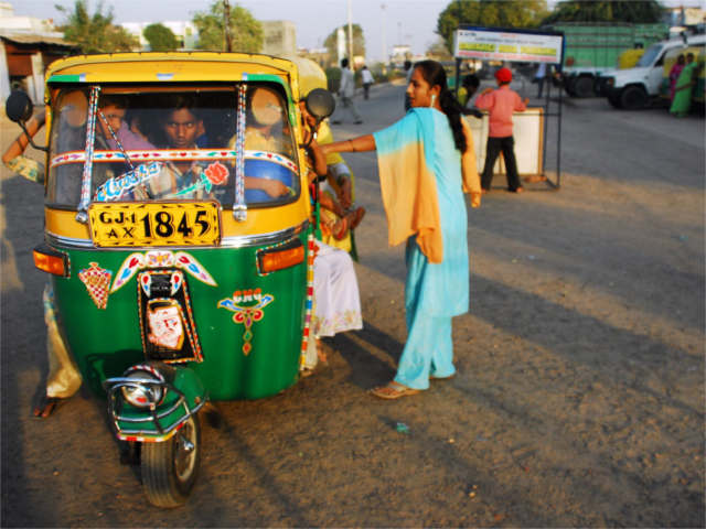 An auto-rickshaw transports passengers in Gujarat, India. Photo by lecercle.