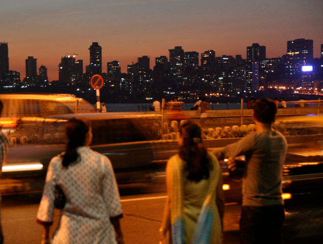 Pedestrians watch traffic in Mumbai
