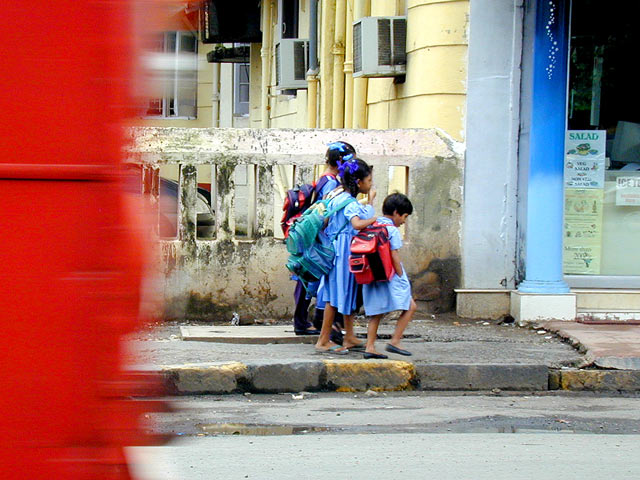 A red bus passes children in uniforms. Transport and integration with the city is key in providing accessibility for all. Photo by Greg Younger.