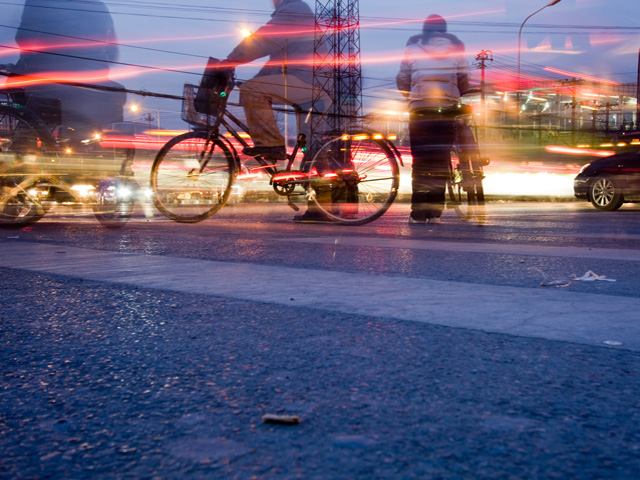 Biker in city night. Photo by Bridget Coila/Flickr