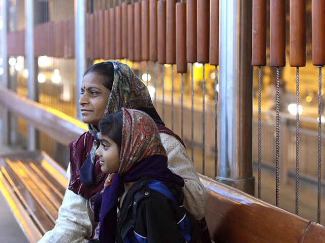 Passengers wait for Ahmedabad, India's bus rapid transit (BRT). Photo by Meena Kadri/Flickr. Cropped.